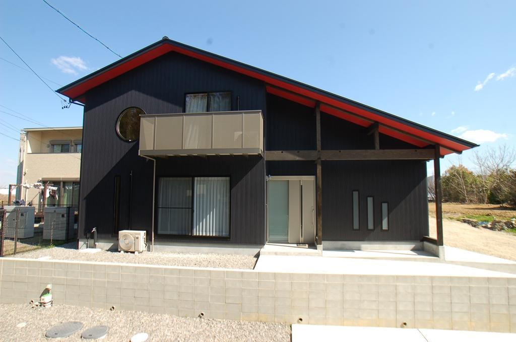 黒い外壁に軒下の赤が映える家